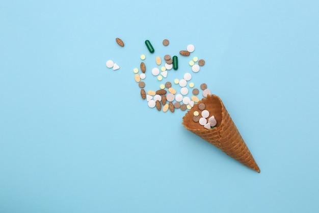 Eiswaffelkegel mit pillen auf weißem hintergrund.