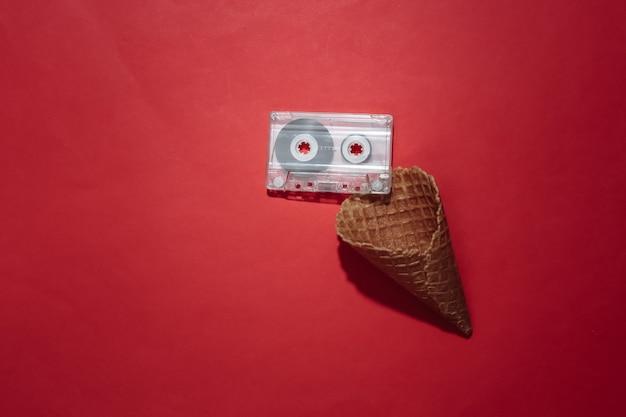 Eiswaffelkegel mit retro-audiokassette auf rotem hellem hintergrund. ansicht von oben