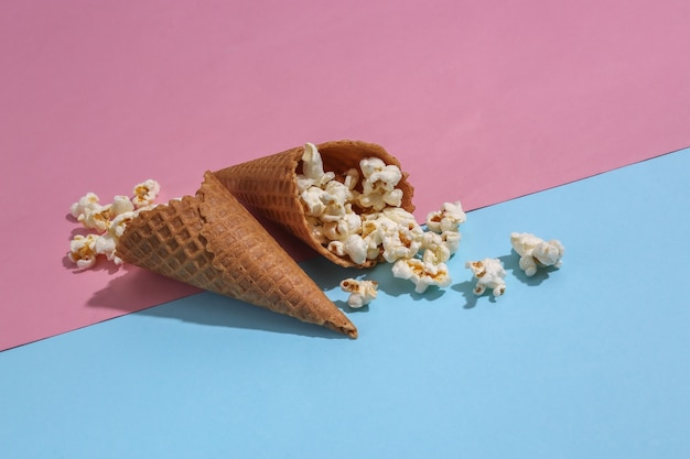 Eiswaffeln mit popcorn auf rosa und blauem hellem pastellhintergrundel
