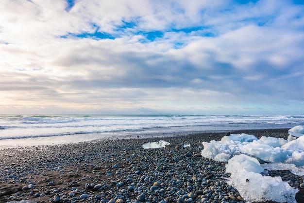 Eiswürfel brechen auf schwarzem rock strand, island winter saison landschaft