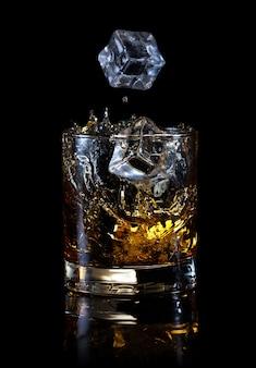 Eiswürfel fallen in glas whisky