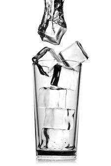 Eiswürfel fielen in glas mit auf weiß isolierten blasen