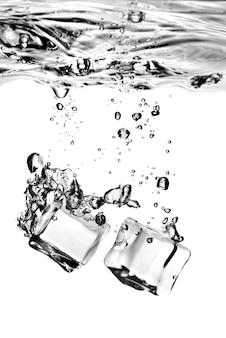 Eiswürfel fielen mit spritzer auf weiß ins wasser