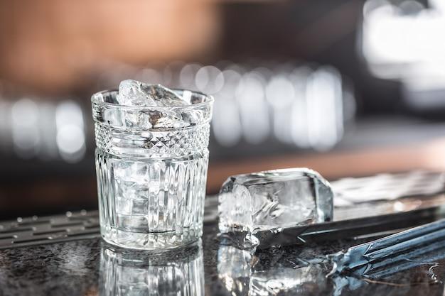 Eiswürfel im glas an der bartheke im nachtclub oder restaurant.