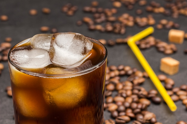 Eiswürfel im glas mit kaffee hautnah. kaffeebohnen auf dem tisch verstreut, gelbes stroh.