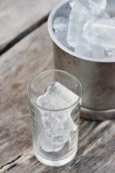 Eiswürfel im glas über holztisch