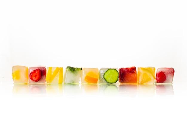Eiswürfel mit früchten auf einem hellen weißen hintergrund. das konzept von heißem sommer, dessert, eis. flache lage, draufsicht