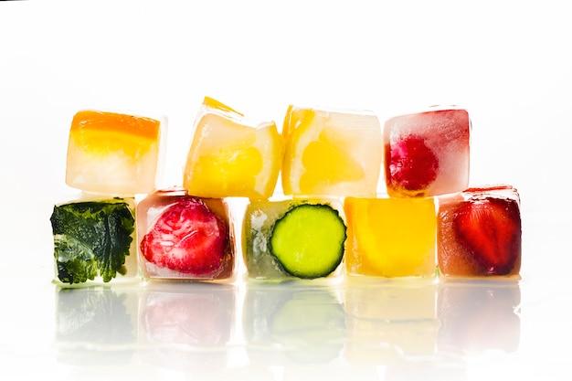 Eiswürfel mit früchten auf einer hellweißen oberfläche. das konzept von heißem sommer, dessert, eis. flache lage, draufsicht