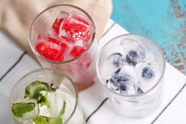 Eiswürfel mit minzblättern, himbeere und blaubeere in gläsern, auf farbiger holzoberfläche