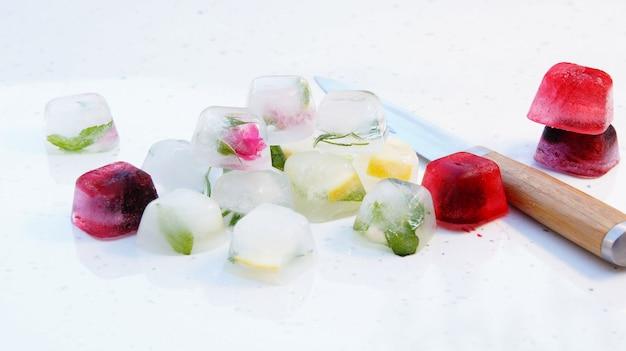 Eiswürfel mit minze, zitrone, rosmarin, thymian, beeren für cocktails und tee