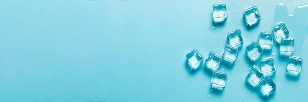 Eiswürfel mit wasser auf blauem grund. eiskonzept für getränke. banner