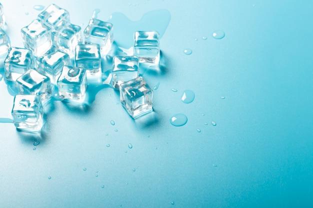 Eiswürfel mit wasser auf blauem grund. eiskonzept für getränke.
