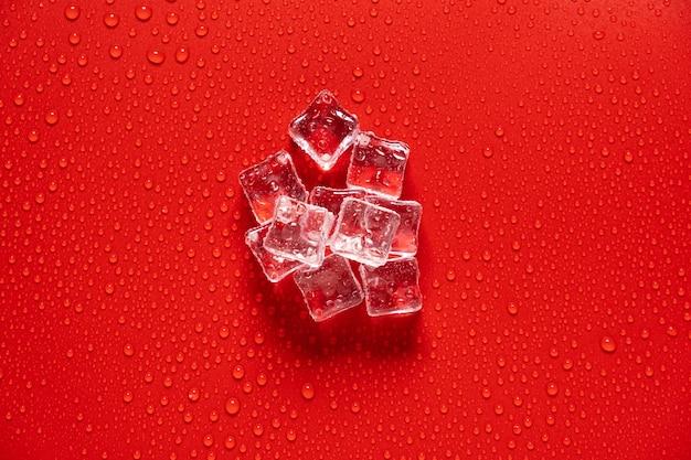 Eiswürfel mit wassertropfen auf rotem grund.