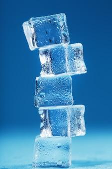 Eiswürfel mit wassertropfen ragen in einer reihe auf blauem grund auf. freiraum