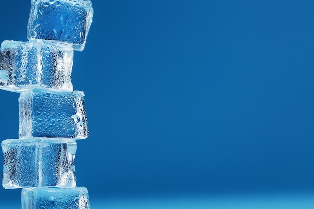 Eiswürfel mit wassertropfen ragen in einer reihe auf blauem grund auf.