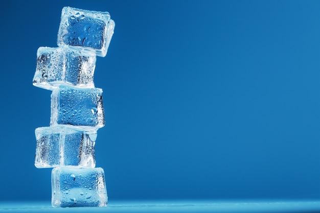 Eiswürfel mit wassertropfen ragen in einer reihe auf blauem grund auf