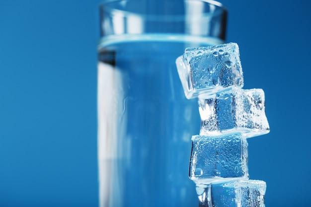 Eiswürfel ragen mit einem glas kaltem und sauberem wasser auf blauem grund auf. freiraum