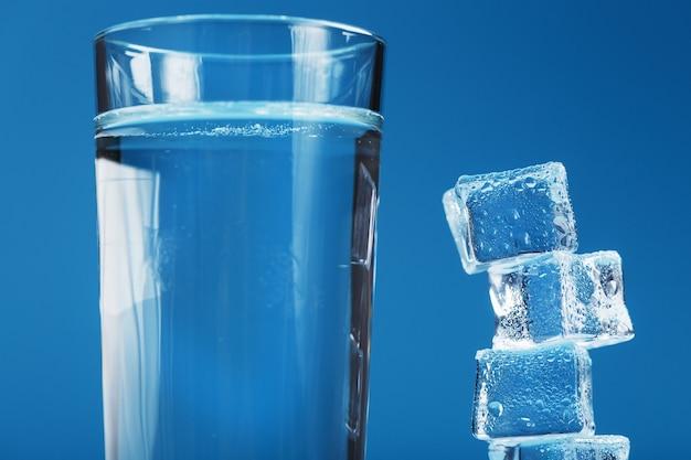 Eiswürfel ragen mit einem glas kaltem und sauberem wasser auf blauem grund auf.