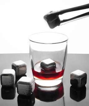 Eiswürfel simulierte stahlwürfel zum kühlen von getränken. wiederverwendbar. silbrig. auf einer dunklen spiegelfläche mit reflexion. neben den würfeln steht ein glas, in das ein stahlwürfel mit einer zange abgesenkt wird.