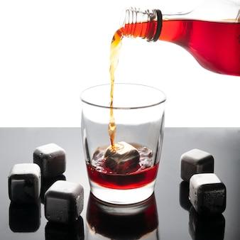 Eiswürfel simulierte stahlwürfel zum kühlen von getränken. wiederverwendbar. silbrig. auf einer dunklen spiegelfläche mit reflexion. neben den würfeln steht ein glas, in das whisky aus der flasche gegossen wird.