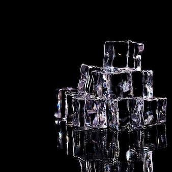 Eiswürfel sind in einer folie angeordnet, isoliert auf einem schwarzen hintergrund.