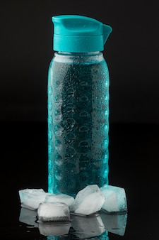 Eiswürfel und fitnessflasche wasser