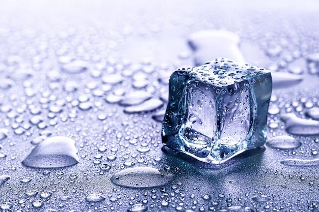 Eiswürfel und wasser schmelzen auf kühlem hintergrund. eisblöcke mit kalten getränken oder getränken.