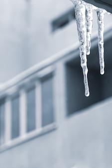 Eiszapfen auf dem balkon, städtischer hintergrund. wintersaison, transparenter eiszapfen am fenster.