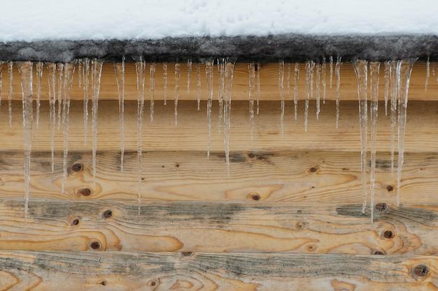 Eiszapfen auf einem hintergrund der braunen hölzernen wand. vorderansicht. platz für text