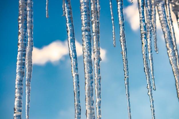 Eiszapfen hängen an einem sonnigen wintertag vom dach