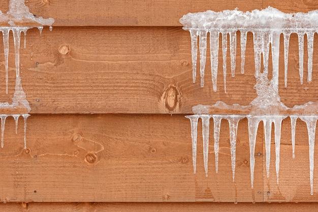 Eiszapfen hängen an natürlicher holzhüttenbeschaffenheit an einer kühlen wintersaison, die zeigen, wie kalt des wetters