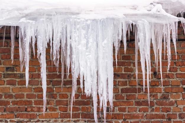 Eiszapfen hängen vom dach des gebäudes - gefahr für menschenleben.