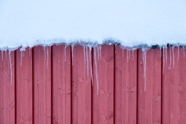 Eiszapfenfrost, der am hölzernen schneebedeckten dach im winter hängt