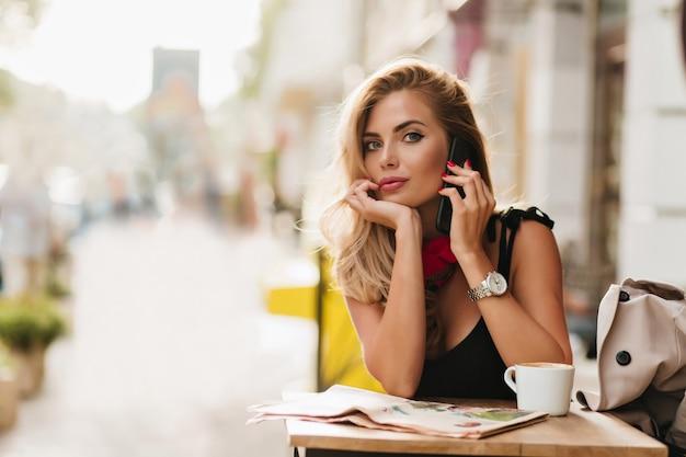 Ekstatische blonde frau, die am telefon spricht und gesicht mit hand nach dem kaffeetrinken stützt
