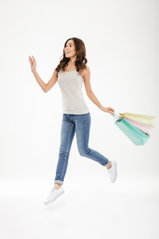 Ekstatische erwachsene frau in voller länge, die in der hand mit lots bunten einkaufenbeuteln, getrennt über weiß frei schwebt oder springt