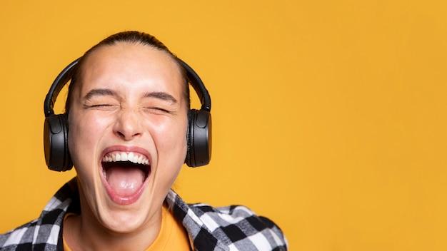 Ekstatische frau, die musik auf kopfhörern mit kopienraum hört
