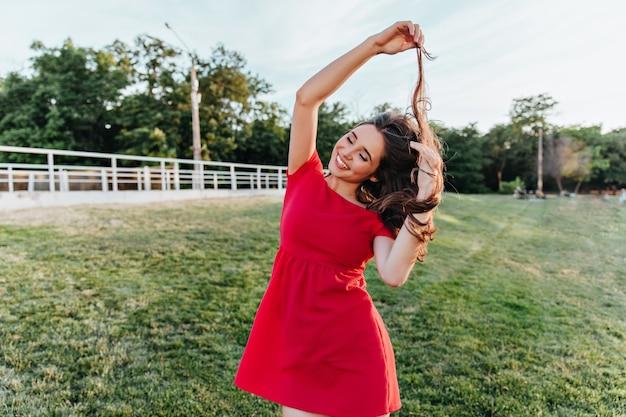 Ekstatische junge dame in der sommerkleidung, die mit ihren haaren während des fotoshootings im park spielt. außenaufnahme des niedlichen mädchens im roten kleid, das spaß am wochenende hat.