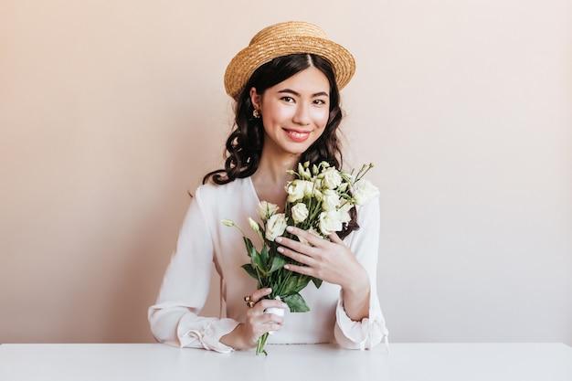 Ekstatische koreanische frau, die beim aufstellen mit blumen lächelt. blithesome lockige asiatische frau, die weiße eustomas hält.