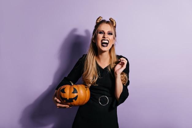 Ekstatische langhaarige frau, die halloween-kürbis hält und lacht. foto des emotionalen vampirmädchens im schwarzen kleid.