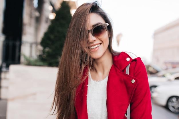Ekstatische langhaarige frau in der niedlichen sonnenbrille, die auf straßenraum lächelt