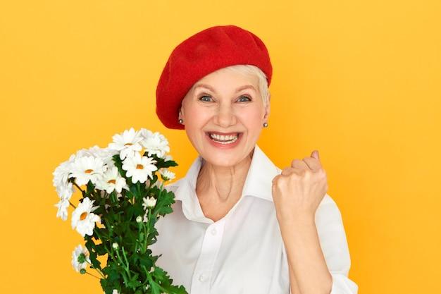 Ekstatische modische reife ältere frau in der roten haube, die einen blumenstrauß hält