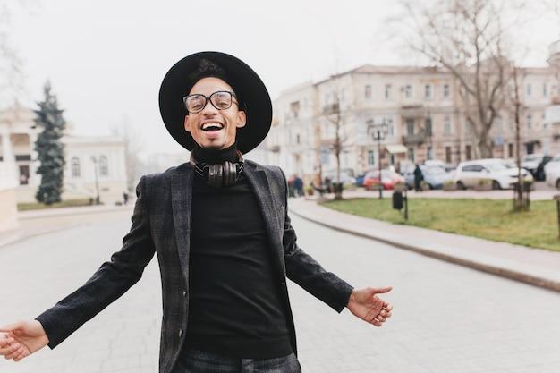 Ekstatischer afrikanischer mann im schwarzen hemd, das in der mitte der straße lächelt. foto im freien des glückseligen männlichen modells im eleganten anzug und im hut, die fotoshooting im park genießen.