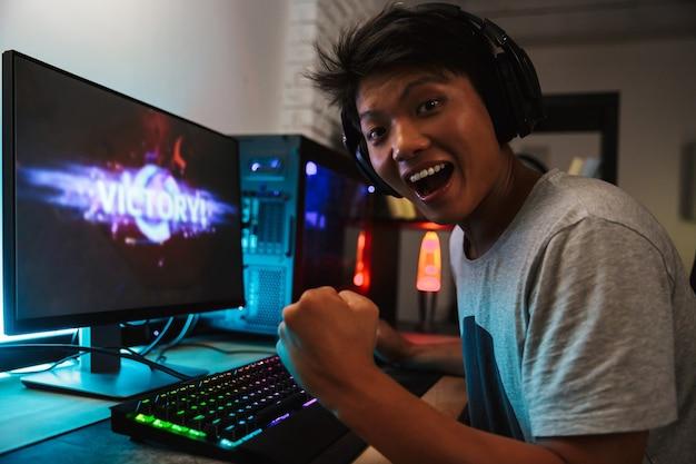 Ekstatischer asiatischer spielerjunge freut sich über den sieg, während er videospiele am computer in einem dunklen raum spielt, kopfhörer trägt und eine hintergrundbeleuchtete bunte tastatur verwendet