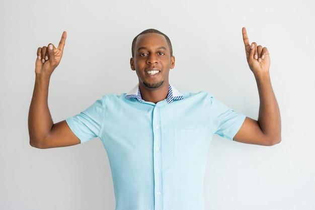 Ekstatischer hübscher afrikanischer mann, der beim empfehlen des produktes auftaucht.