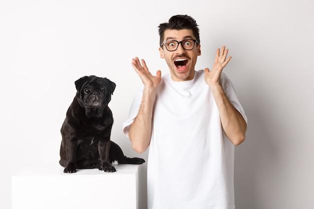 Ekstatischer junger mann, der mit aufregung und freude schaut, in der nähe des süßen schwarzen mops steht, glücklich in die kamera starrt und auf weißem hintergrund steht