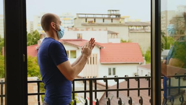 Ekstatischer junger mann mit schutzmaske auf dem balkon, der zur unterstützung des medizinischen personals im kampf gegen covid-19 applaudiert.