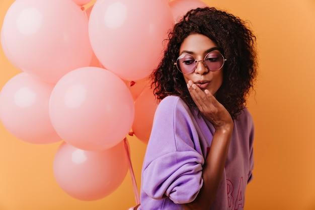Ekstatisches brünettes mädchen in den gläsern, die auf gelb mit luftballons stehen. innenaufnahme der liebenswerten afrikanischen dame, die mit überraschtem gesichtsausdruck aufwirft.
