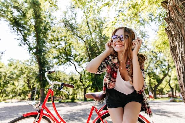Ekstatisches emotionales mädchen, das musik im park hört. außenporträt der fröhlichen europäischen dame, die nahe rotem fahrrad steht und naturansichten genießt.