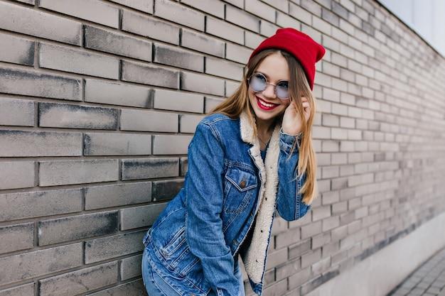 Ekstatisches kaukasisches mädchen in der jeanskleidung und in der blauen brille, die mit niedlichem lächeln aufwirft. erfreute junge frau im roten hut, die während des straßenfotoshootings herumalbert.