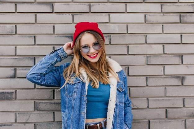 Ekstatisches kaukasisches modell mit hellbraunem haar, das mit lächeln neben backsteinmauer aufwirft. außenporträt der sorglosen jungen frau trägt trendige jeansjacke.